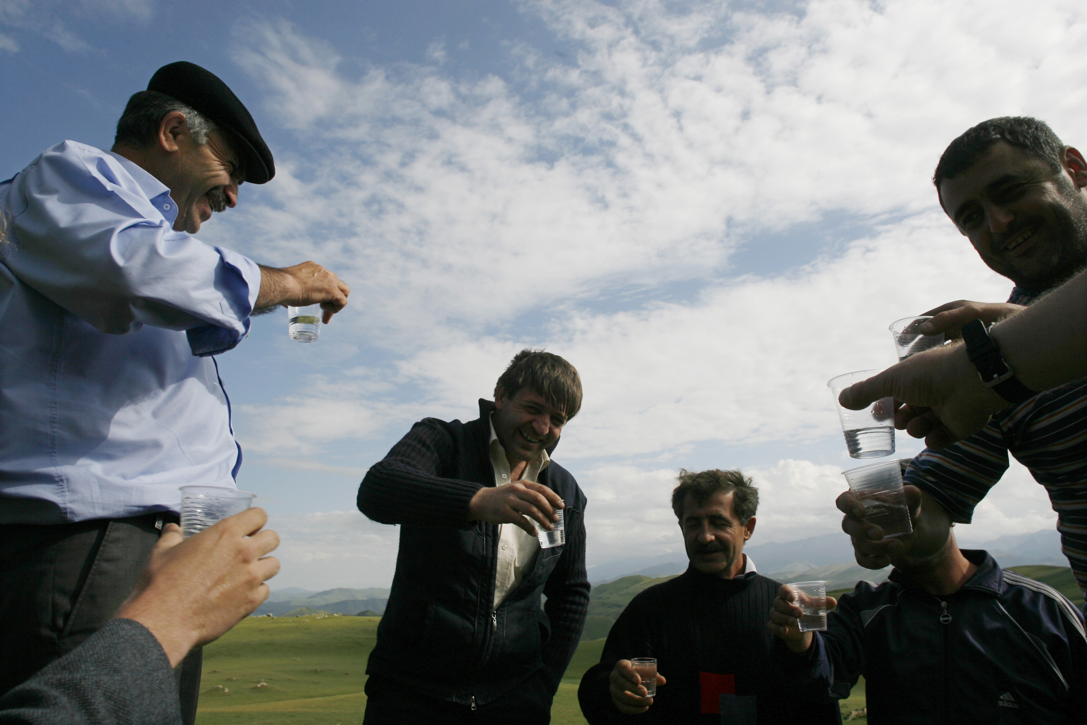 Men drink vodka near the remote mountain village of Tsovkra-1, some 3,000 metres above sea level in Russia's Caucasus region of Dagestan August 20, 2007. For children in this remote mountain village on Russia's southern fringe, after-school games means balancing on a wire suspended one storey above ground. By a quirk of history that goes so far back that in time no one really remembers, nearly every man, woman and child in Tsovkra-1 can walk the tightrope. Picture taken August 20, 2007. To match feature RUSSIA-DAGESTAN/TIGHTROPE REUTERS/Thomas Peter (RUSSIA) - RTR1T7PW
